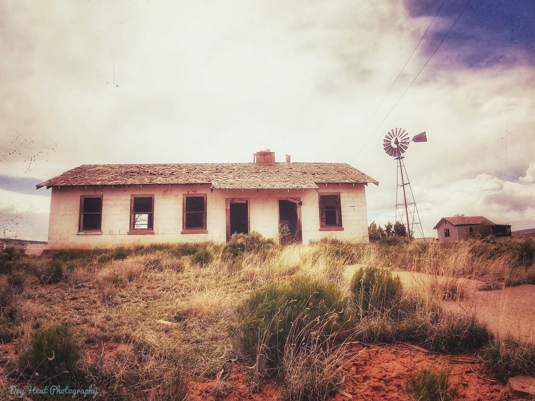 Abandoned farm house with windmill and barn in Ramah, New mexico.